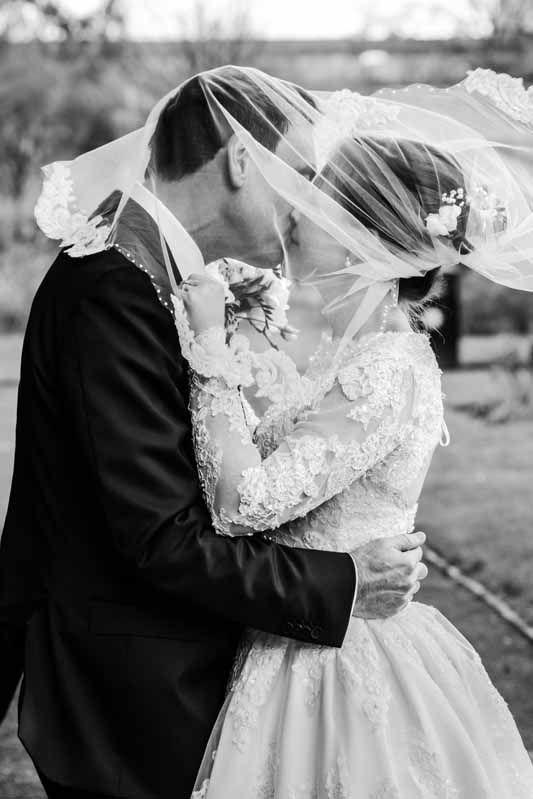 bride groom windy veil kiss